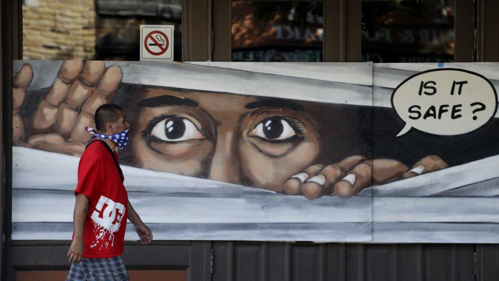 A koronavírus-járvány miatt az arcát kendővel elfedő férfi halad el egy bezárt üzlet falára festett festmény előtt a Texas állambeli Austinban 2020. április 27-én. Greg Abbott, Texas kormányzója bejelentette, hogy enyhíti a járvány miatt bevezetett, a gazdaságot érintő korlátozások egy részét.