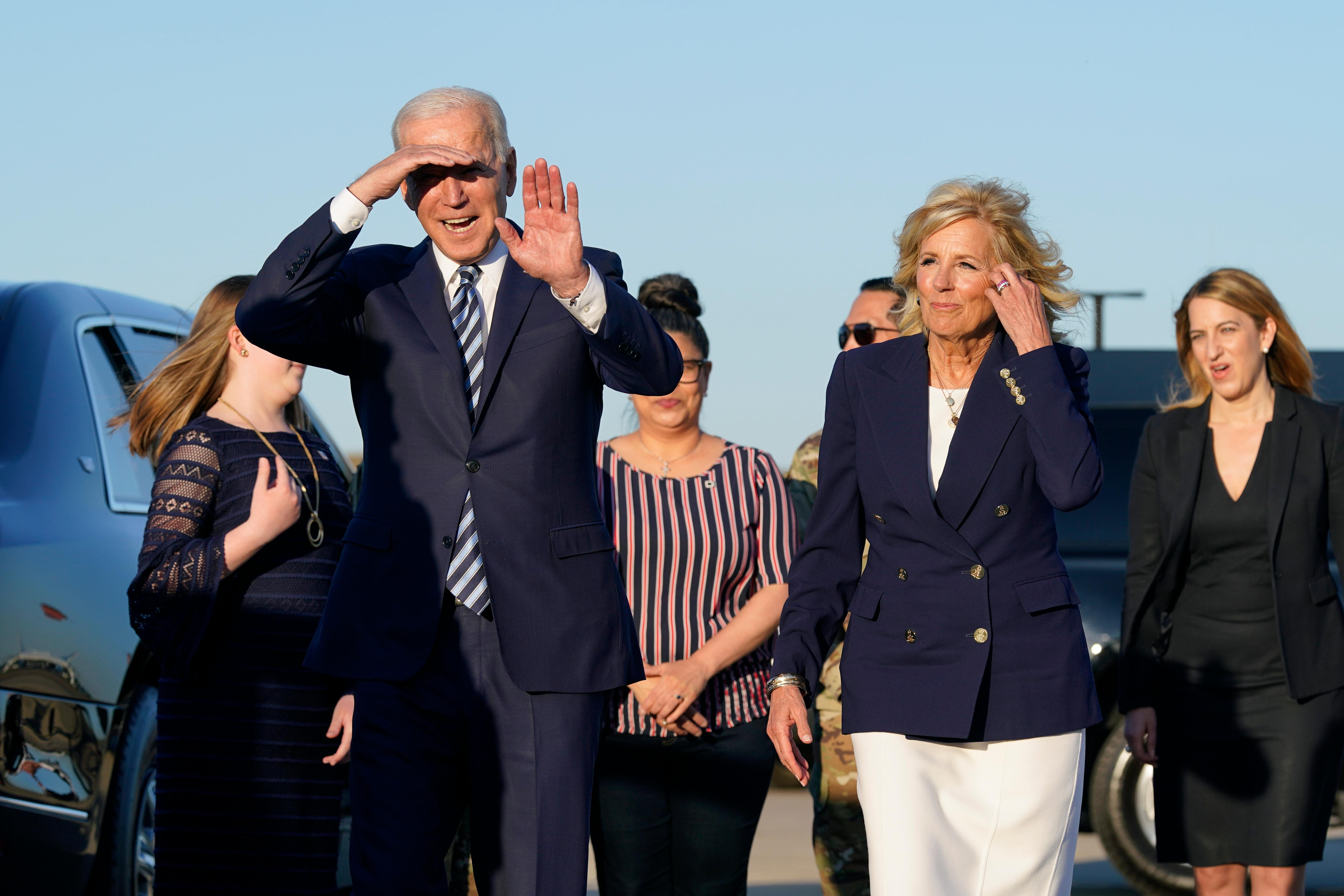 President Joe Biden and First Lady Jill Biden walk to a motorcade car after getting off Air Force One